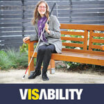 Image of a woman holding a white cane with the VisAbility logo below